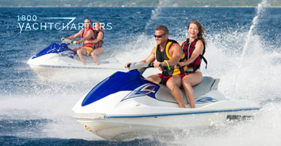 Photograph of 2 couples. Each couple is on a jetski. The jetskis are white with blue front panels. The jetskis are in motion, and they are kicking up a lot of water. Everyone is laughing and having a great time