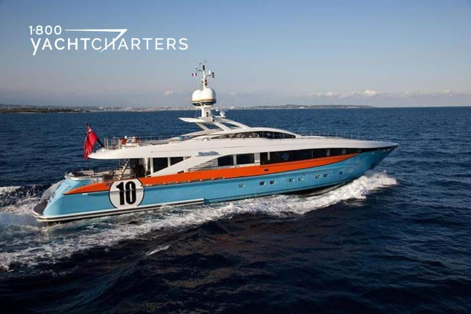Photograph of a colorful motoryacht. It has a light blue hull, orange section at the top of the hull, then a white superstructure. There is a number 10 in black in a white circle, like a racecar, on the side of the yacht toward the back.
