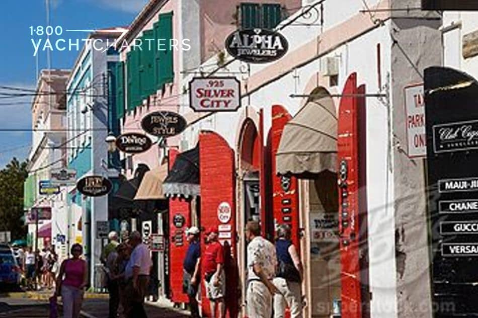 Photograph of people shopping in duty free shops in the United States Virgin Islands. Photo shows a strip of shops with people walking
