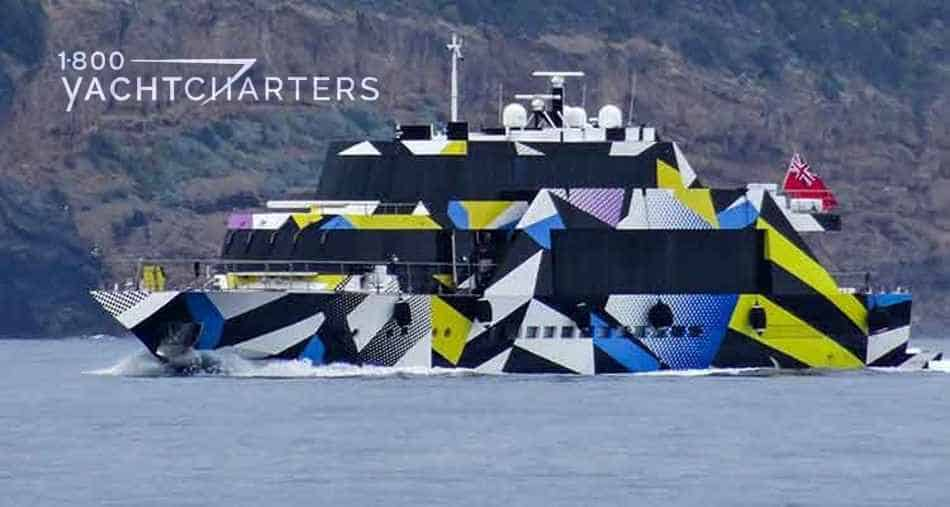 Photograph of a yacht named Guilty that is painted with geometric blocks that are yellow, blue, and black. It is very bright. It is at anchor. It is facing the left side of the photograph.