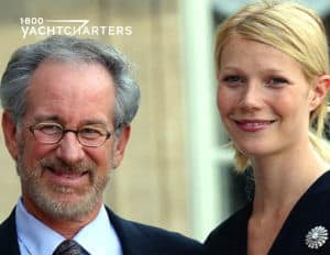 Photograph of Steven Spielberg standing next to Gwyneth Paltrow. He is wearing a black suit with white shirt and black tie. She is wearing a black dress with a silver broach on the left side. They are both smiling. Photo taken before they received Coast Guard fine for yacht coming to close to shore
