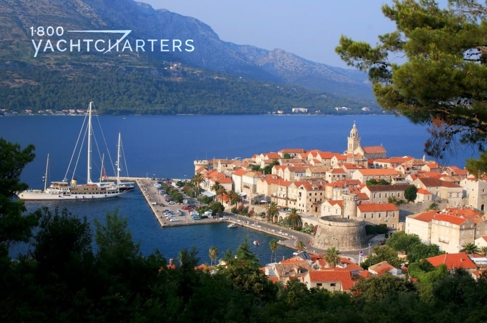 Aerial photograph of Korcula Island in Croatia, Picture shows a huge castle. There are 2 large sailboats docked on the left side of the island. Their sails are down. There is a large wooded island at the back off the picture, across from Korcula.
