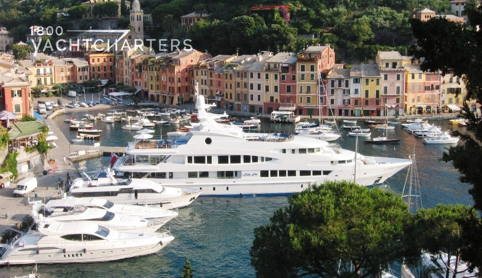 Photograph from land of Lady Lola, a huge superyacht, at the marina in Portofino, Italy, with many other yachts.