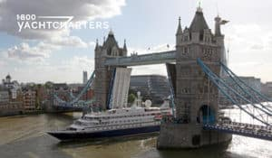 Photograph of a yacht going under the London Bridge on the Thames River