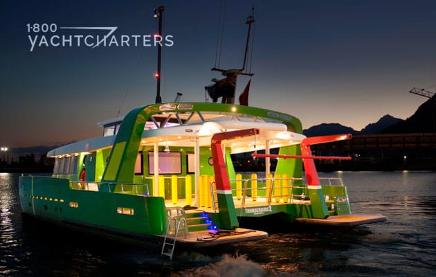 Night photograph of a powercat with a unique paint job. It is painted green on the outside, with yellow and red highlights on the doors and exterior of the yacht. Bright night lighting highlights the yellow doors