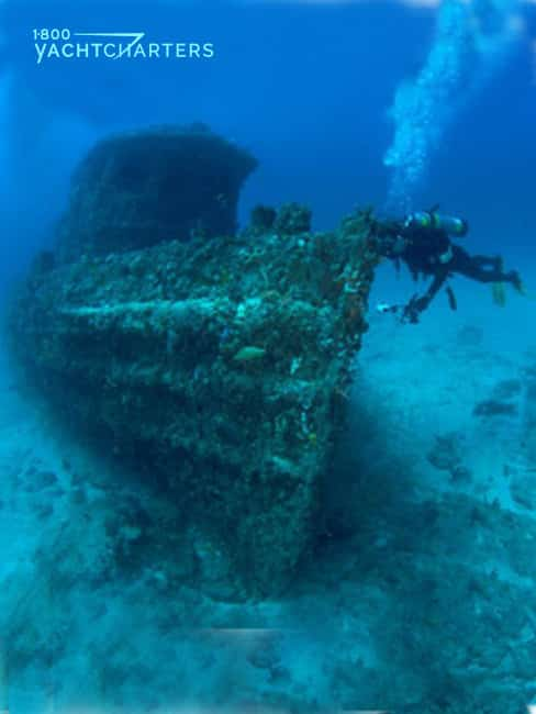 Photograph of a scuba diver swimming next to a dive site of a sunken ship called the Tugboat Jay Scutti in Ft. Lauderdale, Florida