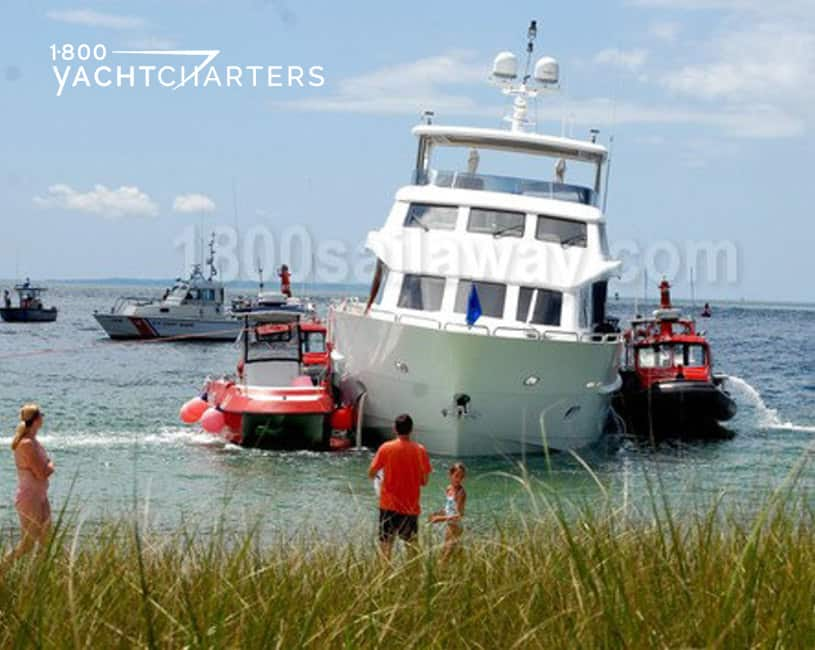 Photograph from the land of a yacht that ran aground. It is close to shore. There are 2 red tugboats on either side of the yacht. The white yacht is leaning to the right side of the photo.  2 people dressed in black and red are watching from shore. There is a ship at anchor in the background.