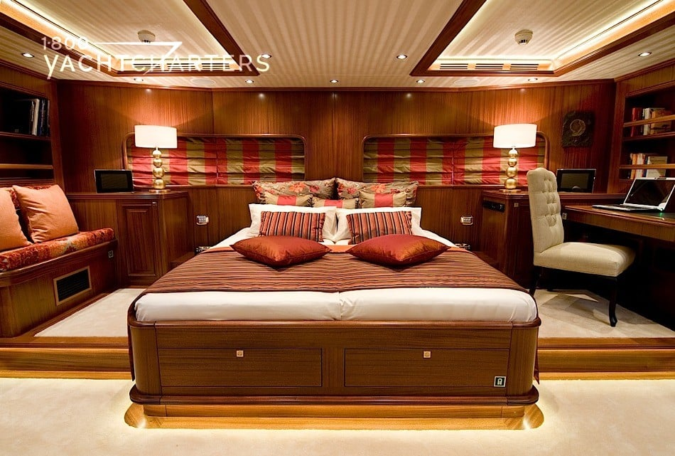 Photograph of the master stateroom of sailboat CLEAR EYES.  Light colored carpet, chestnut brown walls, bed with rust-colored throw pillows.