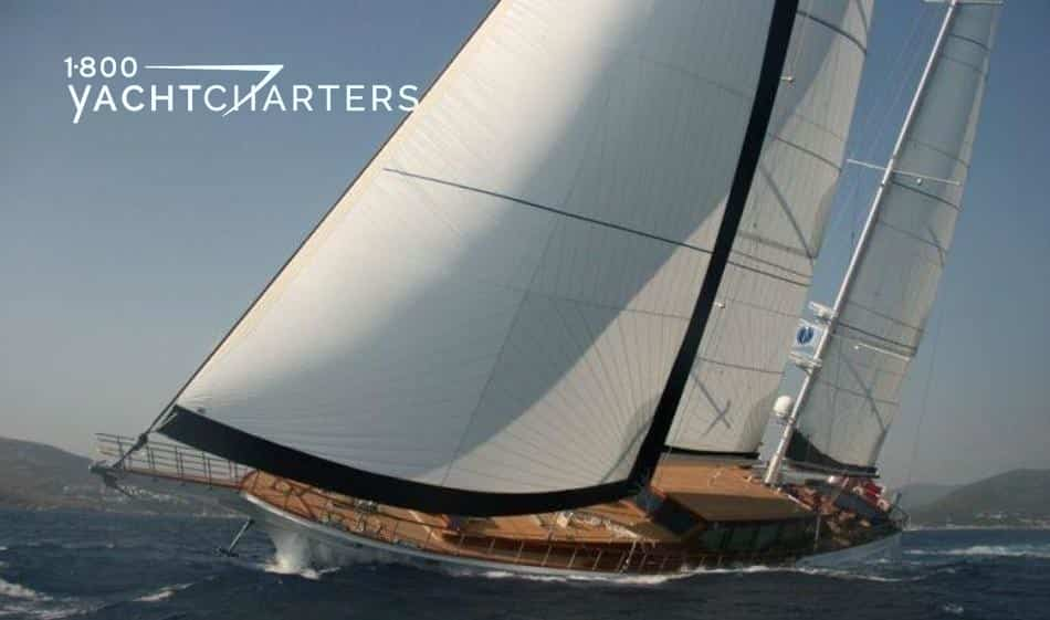 Photograph of sailboat CLEAR EYES underway.  It has white sails with black trim.  The boat hull is white, and the deck is chestnut brown. The boat is leaning toward the front of the screen, and it is sailing toward the lower center of the left side of screen.