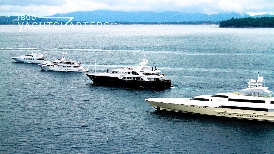 Aerial photograph of four motoryachts traveling next to each other. They are in staggered order. On a diagonal. They are on a calm sea, and there is a mountain at the back right side of the photo.