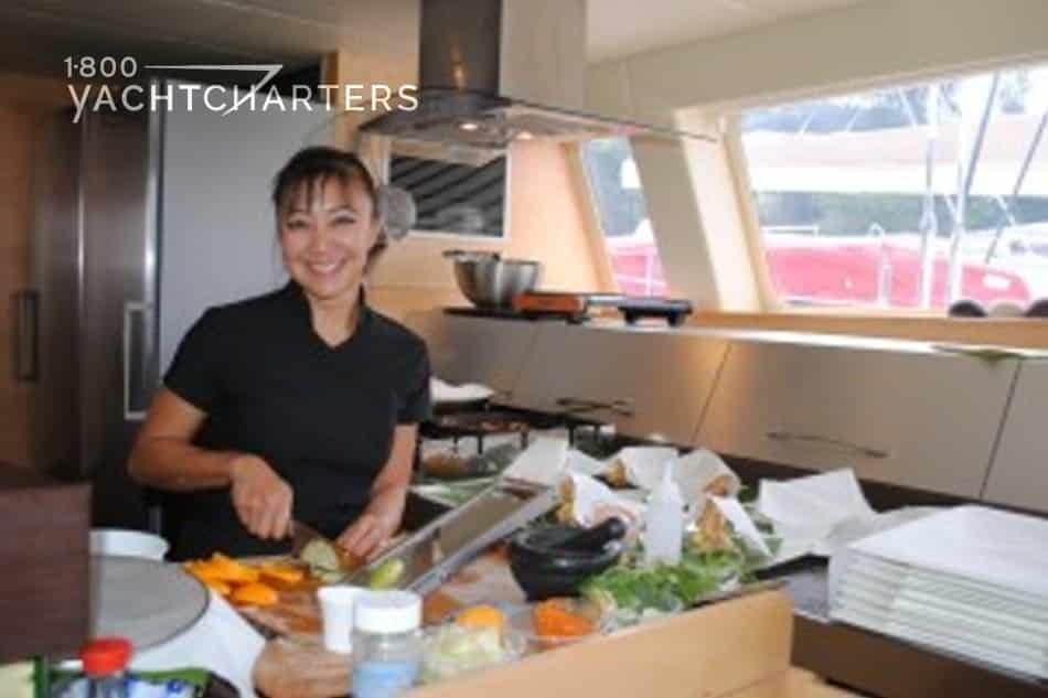 Photograph of chef in kitchen of catamaran sailboat. She is wearing dark t-shirt. She is very pretty, has dark hair and dark eyes. You can see that the sailboat is in a marina, as there are other boats seen out the windows behind her.