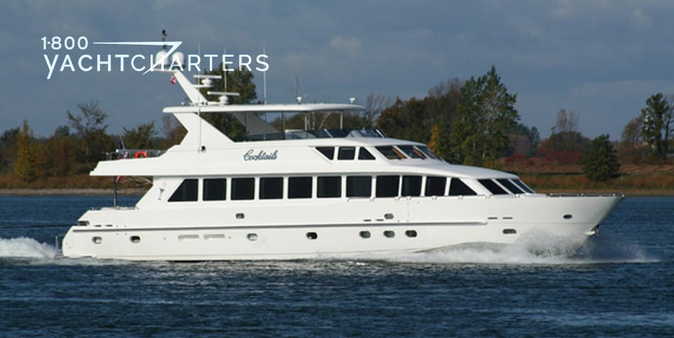 Photograph of yacht Cocktails profile.  The yacht is headed to the right side of the picture.  There is a large green mountain behind the yacht. The yacht is solid white with multiple small windows that are square, triangular, and oblong.