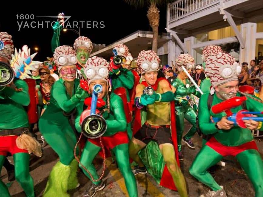 Photograph of a group of musicians dressed in green lycra jumpsuits with red skirts and fringe. The musicians are all men, and they are all laughing and enjoying playing their brass instruments.