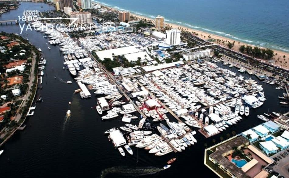 Aerial photograph of the Fort Lauderdale International Boat Show marinas.  At least 300 big white boats in marinas.  Dark canal water on the left side of the marina.  Yachts in the center.  Roadway on the right of the marina.  Sand and turquoise ocean on the far right side of the photograph and marinas.
