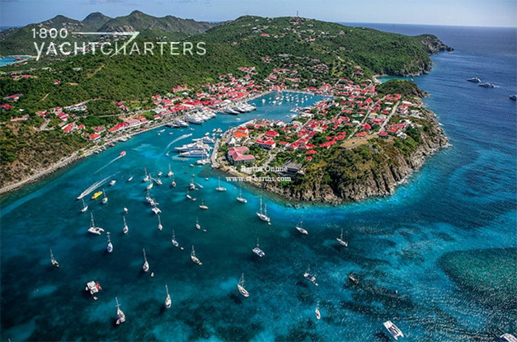 Aerial view of the island of St Barts in the Caribbean. There are many sailboats and motoryachts at anchor and in the marina.