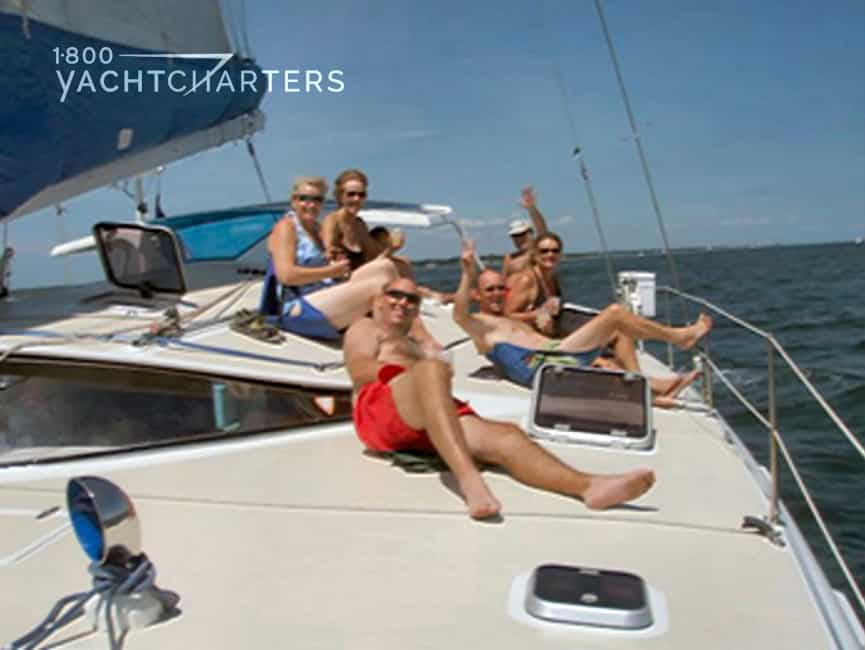 Photograph of smiling guests laying on the deck of a catamaran sailboat. The sun is shining.  The sea looks calm.