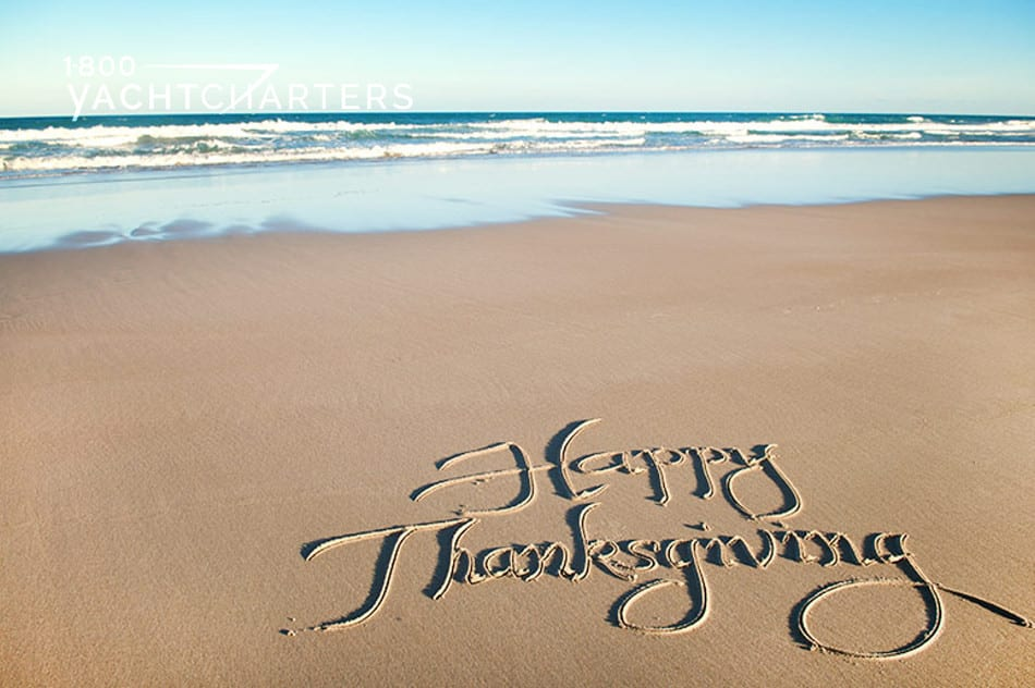 Photograph of the words, Happy Thanksgiving, written in the sand. The ocean lapping in the background.