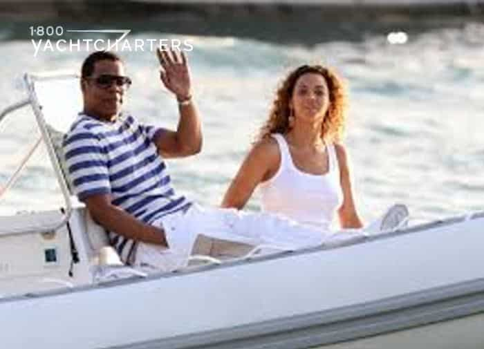 Photograph of Jay Z and Beyonce on a boat ride. JayZ is wearing a blue and white horizontally striped short sleeved shirt and white pants. Beyonce is wearing a white tank top and her long hair is down. Jay-Z is waving to the camera. Beyonce is smiling.