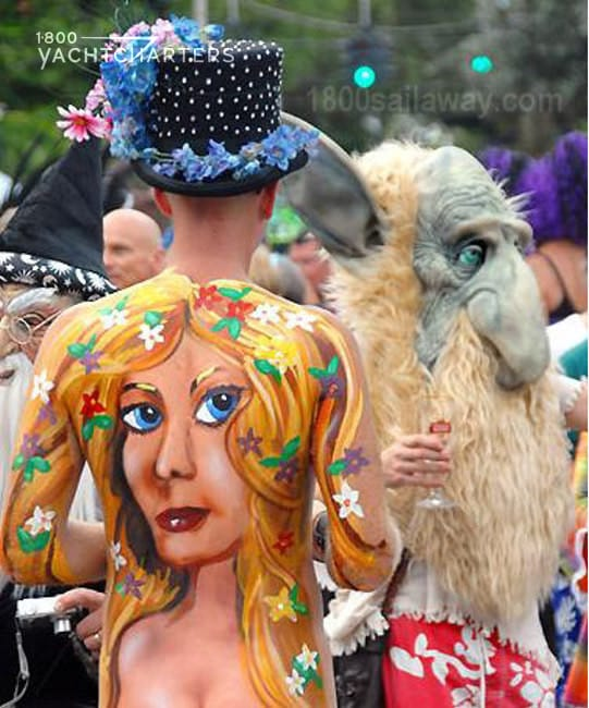 Photograph of a man with a woman painted on his bare back at the Florida Keys Key West Fantasy Fest. The girl is blonde with green and yellow flowers in her hair. He is wearing a black top hat with liht blue flowers around the brim.