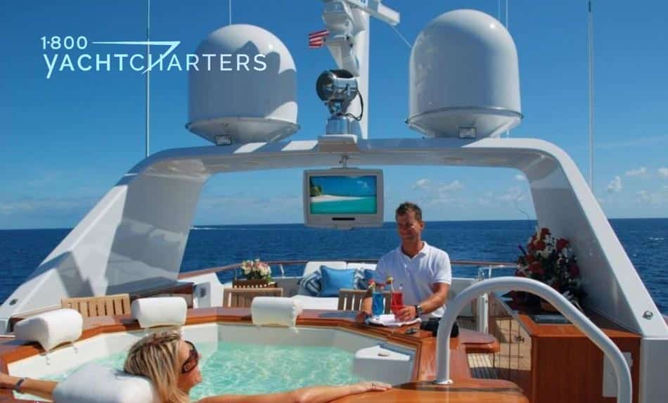 Photograph of a woman relaxing in an on deck jacuzzi tub on yacht Lady J. A crew member in white shirt watches over her. There is a television screen in the background. She can see it from the hot tub. The crewmember and she are both smiling