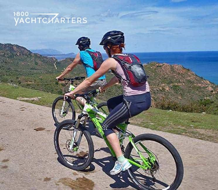 Photograph of a man and a woman riding bicycles on a cliff overlooking the ocean. Beautiful scenery. As if they are on a yacht charter and are adventuring on bikes above the yacht