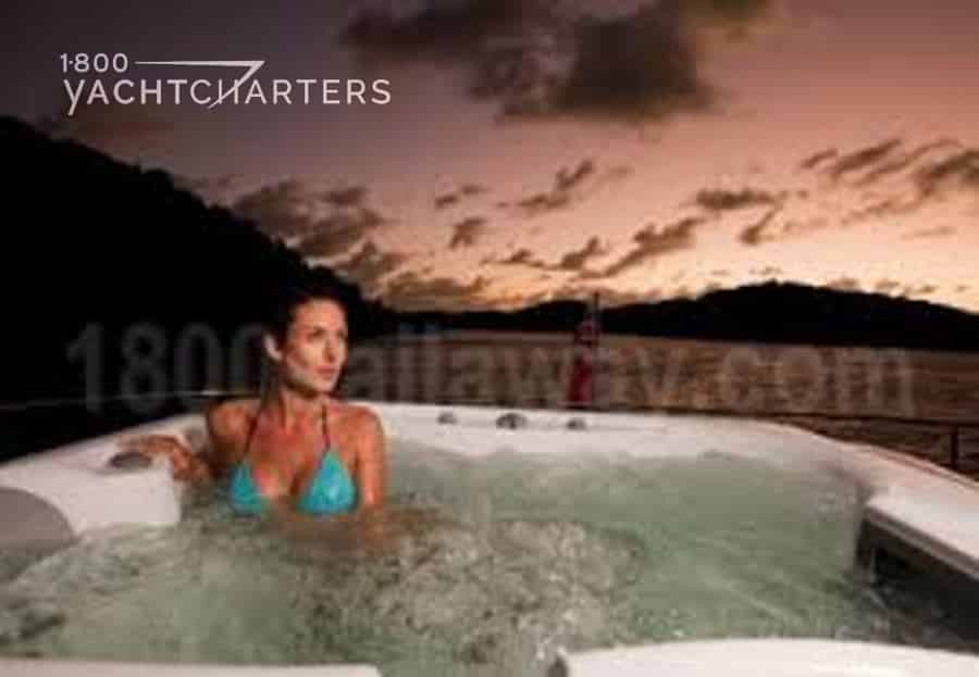 Photograph of a woman in a hot tub on the yacht named Sea Bass. She is wearing a turquoise bikini. It is sunset. There is a dark mountain behind the yacht.