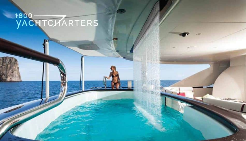 photograph of waterfall swimming pool on motoryacht Quinta Esentia. Blond woman in red bikini stands seductively on the other side of the pool. Water is plunging into the pool from the waterfall.