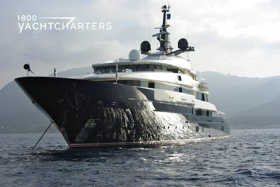 Photograph of motoryacht Seven Seas. The yacht is facing the bottom left side of the photo, with a focus on the bhow of the yacht. There is a reflection of the sun on the dark bow. The yacht has a white superstructure.