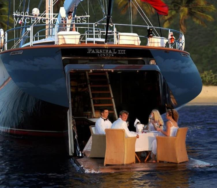 Photograph of yacht charter guests dining on the swim platform of a huge dark blue-hulled Perini Navi sailing yacht. Photo taken from the waterline of the yacht.