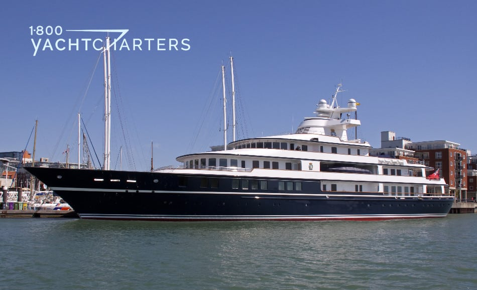 Profile photograph of Leander G, a yacht with a dark blue hull and red stripes.  She has a white superstructure. She is at anchor in front of some old brick buildings.