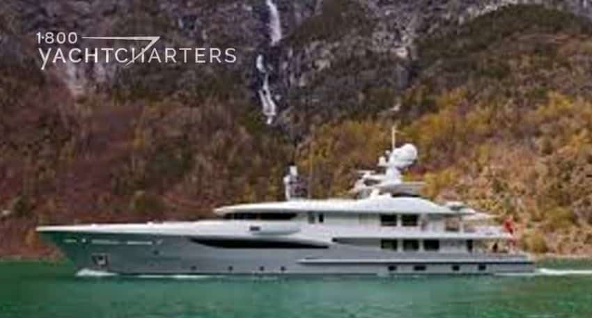 Photograph of a yacht with a light grey hull, at anchor in front of a mountainside with waterfalls coming down the center of the mountain. The yacht is facing the left side of the picture. The water is green. The mountain is brown. Looks cold.