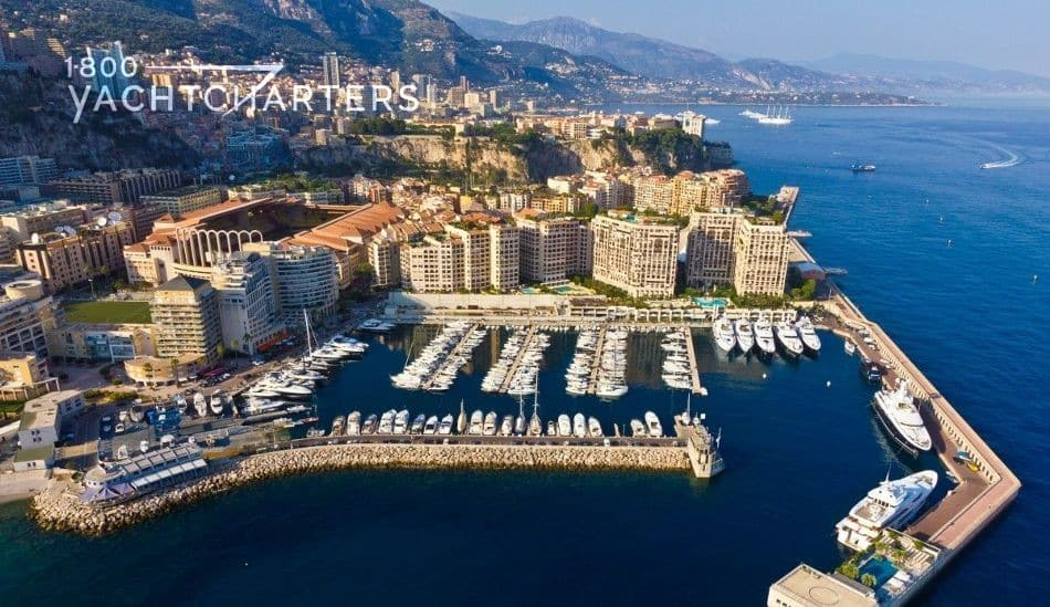 Aerial photograph of a marina in Monaco. Shows multiple motoryachts on extended slips.