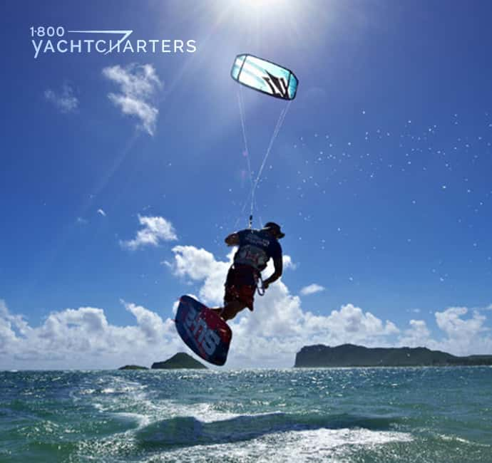 Photograph of a man kitesurfing. He is airborne. His kike is fully-inflated. He is over the water, and his shadow is below him. The sun is shining overhead, and there is a mountain in the distance.