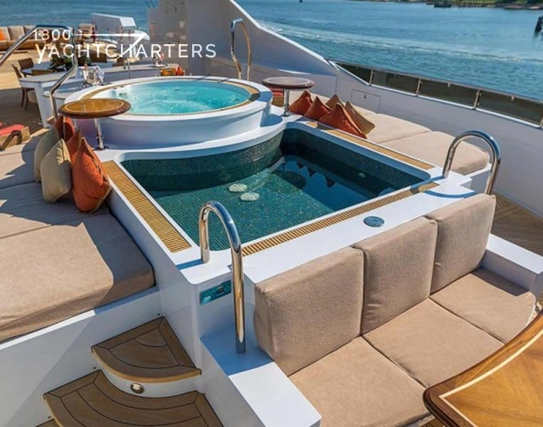 Photograph of deck hot tub and spa pool on a yacht. Beige plush cushions on all seats around tub.