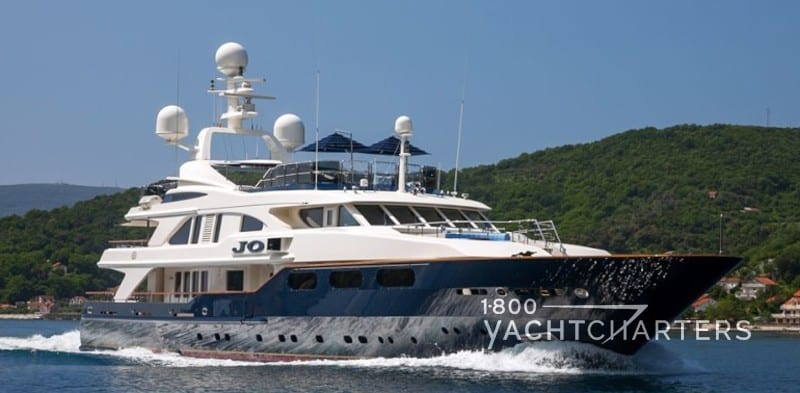 Profile photograph of blue-hulled motor yacht JO underway. She is horizontally headed toward the lower right side of the photo. The Superyacht Experience(tm) created by 1800yachtcharters