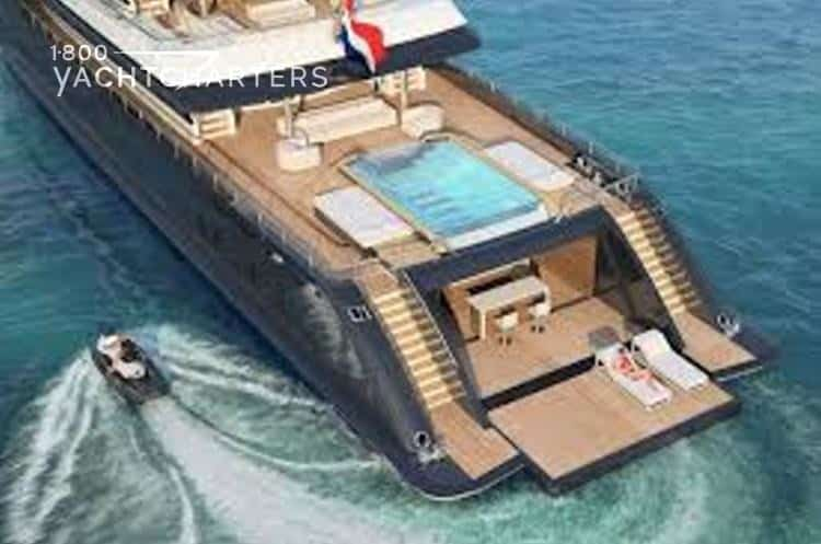 Aerial photograph of the yacht, Icon. Her beach club aft deck is pulled out and has 2 sun loungers on it, ready for people to lay in the sun.