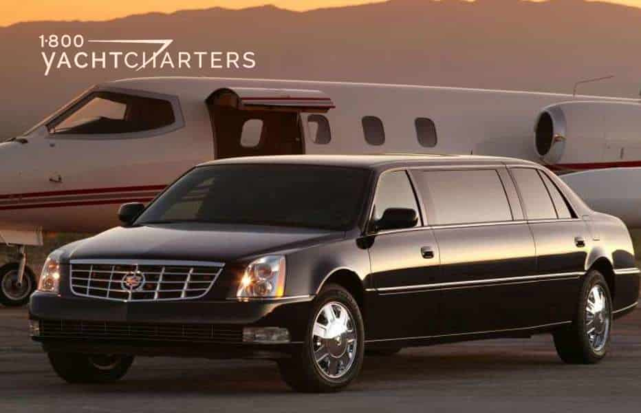 Black Cadillack limousine parked next to a small plane with the door open. Sun is setting in background of photo. Mountains in background. Car and plane both on airport tarmac