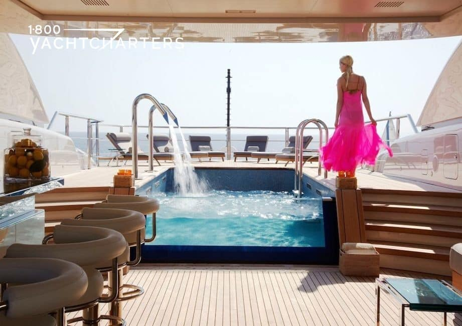 Photograph of the hot tub on superyacht Numptia. There is a woman in a pink flowing dress standing on the edge of the tub. There is a waterfall swifly flowing into the tub.