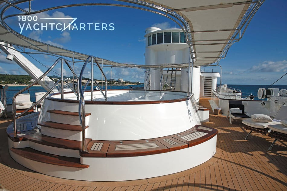 Photograph of the hot tub on superyacht SHERAKHAN. Double-decker tub with stairs and silver rails leading up to it.