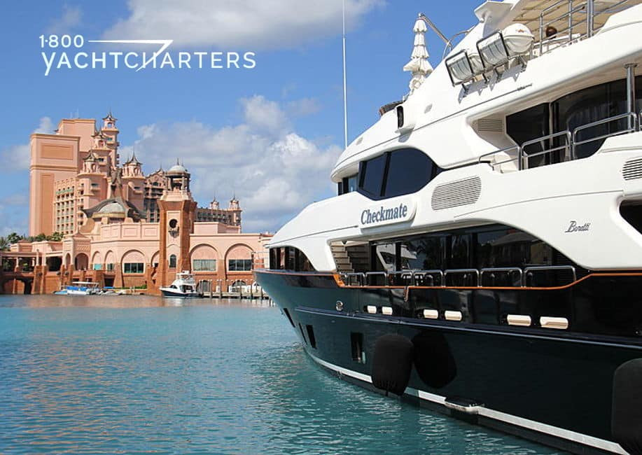 Photograph of motoryacht Checkmate heading towards Atlantis in the Bahamas. The yacht is on the right side of the photo. All that you see is the black hull of the yacht and white superstructure. The yacht is facing approximately 11 o'clock in the photo, if the photo were the face of a clock. Atlantis, the resort, is at the top left corner of the photograph.
