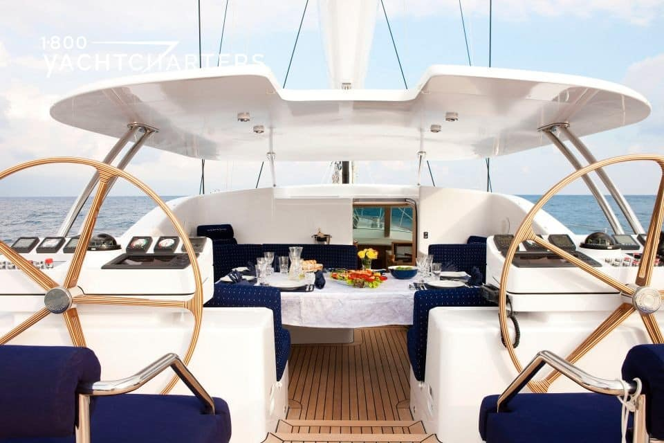 Photograph of the cockpit of sailboat NOSTROMO. Photo taken from the back of the yacht. Photo shows two sailboat ship's wheels in the foreground, with cockpit dining table in the background, covered by white awning. The table is set for dining.