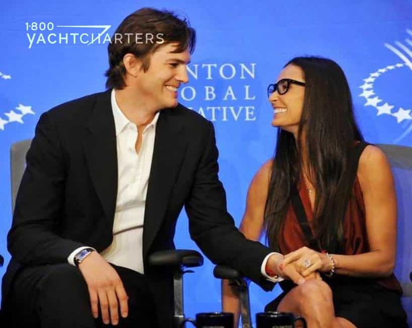 Photograph of Ashton Kutcher and Demi Moore sitting in front of a blue backdrop. They are looking at each other and laughing.