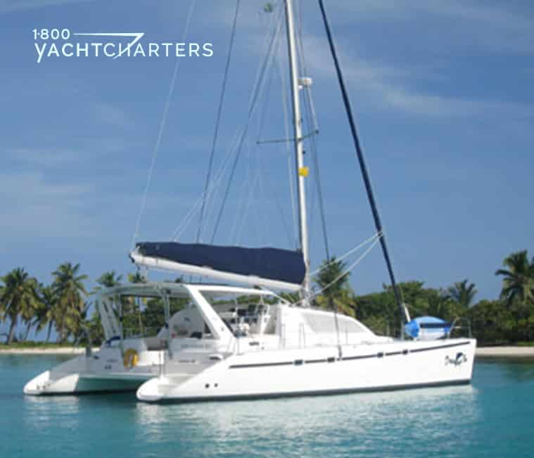 Photograph of catamaran sailboat DREAMING ON at anchor. She is facing the right side of the screen. Her sails are down.