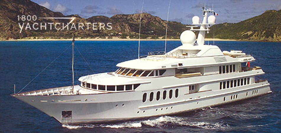Photograph of superyacht Huntress underway in deep blue water in front of a large brown mountain