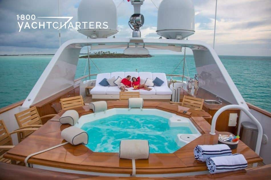 Photograph of the sundeck of superyacht Lady J.  It has a hot tub that is surrounded by caramel-colored sunpads.