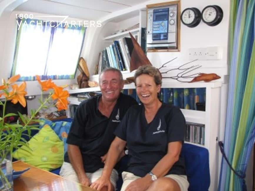 Photograph of John and Sue, the crew of sailboat, Makayabella. They are sitting in the living room on a sailboat. The walls are white and full of books and pictures with brown picture frames. They are both wearing dark blue polo shirts with sailboat logos on the left chests. They are wearing white shorts.