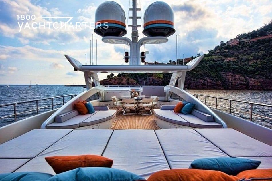 Photograph of sundeck of motoryacht, Aurelia. The sunpads are white, and the neck cushions are orange and turquoise, to match the colors of the yacht's hull. There are 2 large satellite balls visible at the top of the yacht.