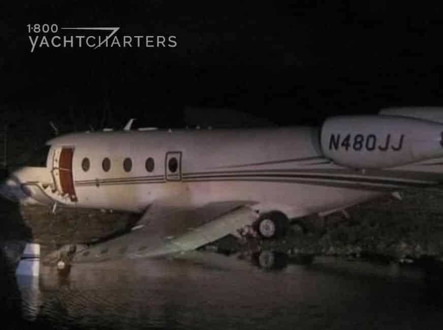 Dark photograph of a private jet that crashed.  Entire jet is still in one piece, but one wing is in a canal.