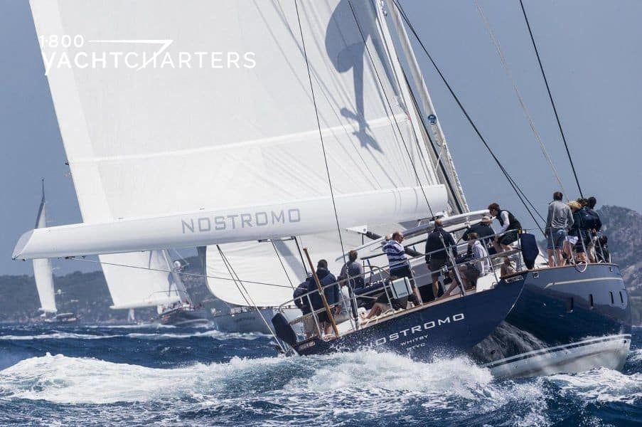 Photograph of the back of sailing yacht NOSTROMO during a sailing race. She has a white sail and a shiny blue hull, and there are multiple sailors on deck who are helping race the boat. There is a large wave behind her, indicating fast speed