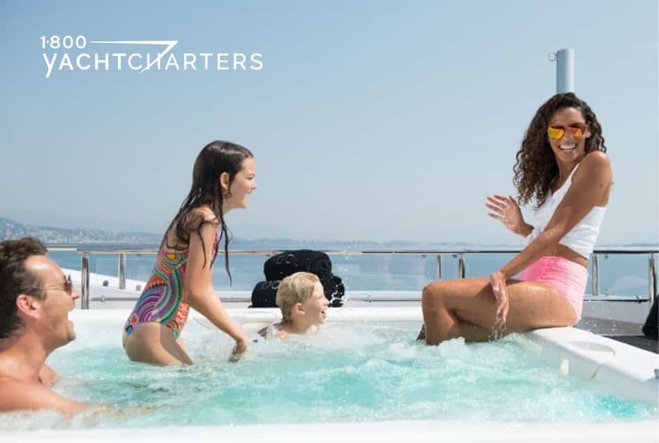 Photograph of a family in the ondeck hot tub of a yacht. The mom is sitting on the edge, and the little girl is standing in the hot tub and splashing her. The little boy is sitting in the water, and the dad is in the jacuzzi and laughing at the antics of the family